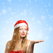 Young woman in santa claus hat with christmas greeting card