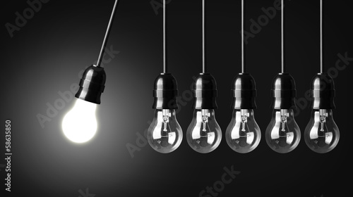 Idea concept on black. Perpetual motion with light bulbs - 58635850