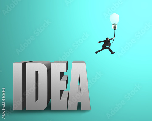 Businessman jumping from idea concrete word to catch glowing lam