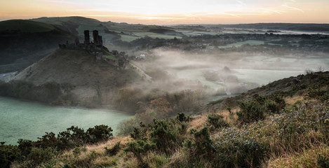 Medieval castle ruins with foggy landscape at sunrise