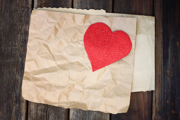 red heart on a crumpled brown paper on wooden background