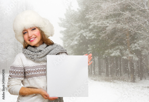 Girl with empty poster at winter forest