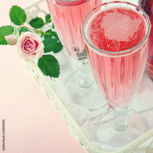 Glasses of pink champagne with a rose
