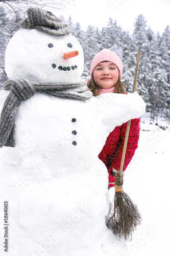 Snowman and a young girl outside in snowfall