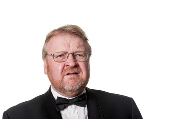 Frowning middle aged man in tuxedo on white