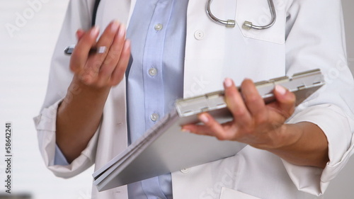 Close up of doctor's hands writing on medical chart