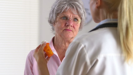 Elderly patient talking to doctor about medication pill bottle