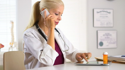 Female doctor talking on mobile phone about prescription bottle