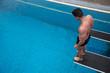 Schwimmer springt von einem Sprungturm in Badeanstalt