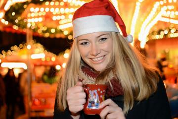 Frau mit Nikolausmütze trinkt Glühwein