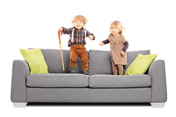 Brother and sister siblings standing and playing on a sofa
