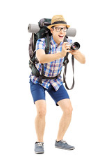 Male tourist with backpack taking a picture with the camera