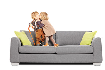 Girl kissing a boy while standing on a sofa