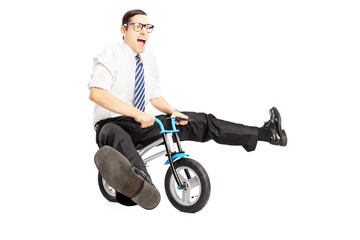 Nerdy young male with tie riding a small bicycle