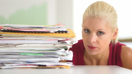 Business woman pushing away large pile of paperwork