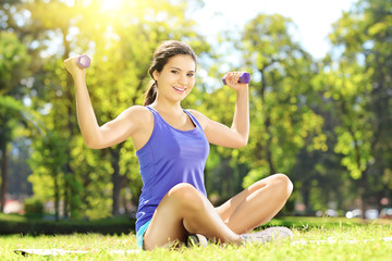 Young female seated on a grass exercising with dumbbells in a pa