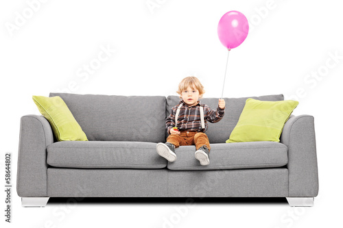 Cute little boy sitting on sofa with a hot air balloon