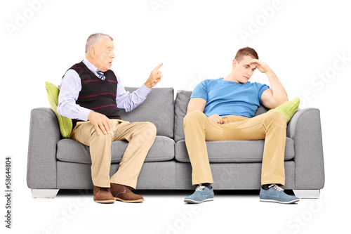 Father reprimending his son seated on a couch