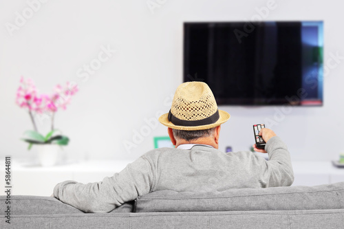 Man with hat sitting on a sofa and changing channels at home