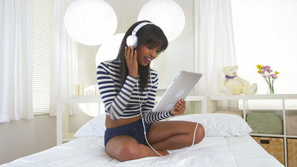 Cute black girl listening to headphones and having video chat on