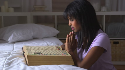 Black girl praying with Bible on bed