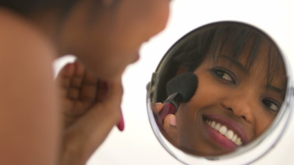 Black girl applying makeup in mirror
