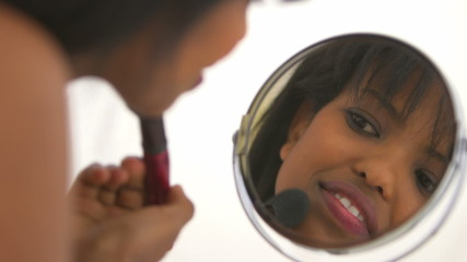 African American girl applying makeup in mirror