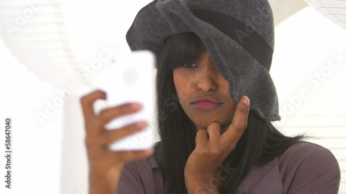 Black girl taking self shots with phone while wearing stylish ha