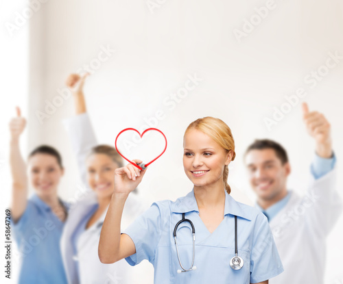 Fototapeta smiling doctor or nurse drawing red heart