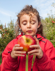 small girl with a freshly picked apple