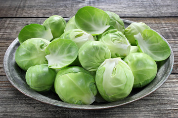 Brussels sprouts in metal bowl on wooden table