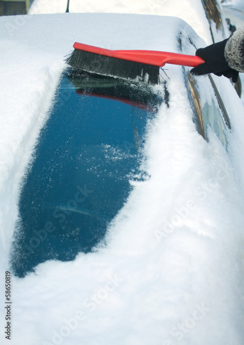 Woman's hand in black garment brushing snow from car