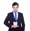 Handsome businessman holding a piggy bank, isolated on a white b