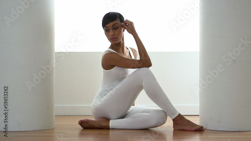 African American woman sitting on floor in white singlet
