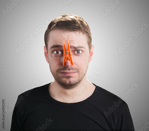 Man with clothespin on his nose - bad smell concept.