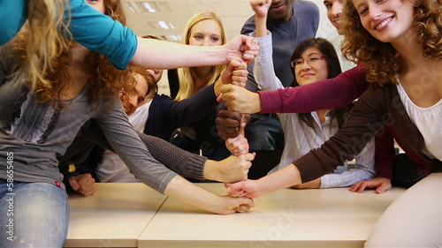 Students stacking fists in school