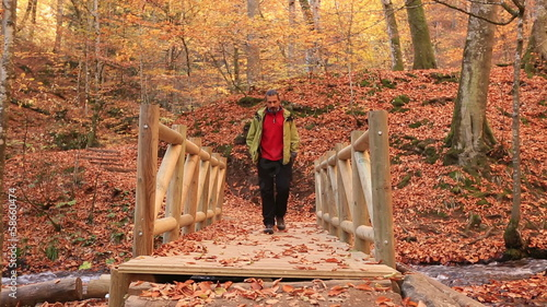 man hiking and passing bridge at forest in autumn season