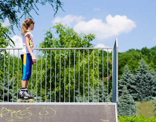Teenage girl in rollerblades on a ramp