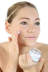 Frau trägt Gesichts-Creme auf