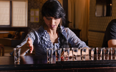 Female alcoholic downing a row of shots