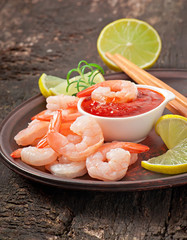 tails of shrimps with fresh lemon and rosemary in ceramic plate