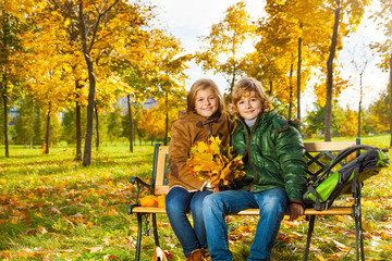 Two kids with bouquet of maple leaves