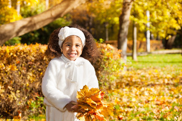 Little girl with bunch of yellow leaves