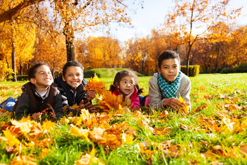 Four kids lay in autumn leaves