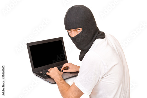 Man in black mask looking at camera and typing something