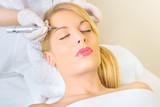 Fototapety Cosmetologist applying permanent make up on eyebrows