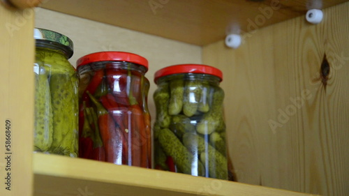 hand takes small jars pickled onion garlic and capers from shelf