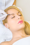 Cosmetologist applying permanent make up on eyebrows poster