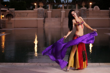 Belly Dancer in Red Costume Dances with Purple Veil