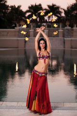 Belly Dancer in Red Costume with Fire Fans